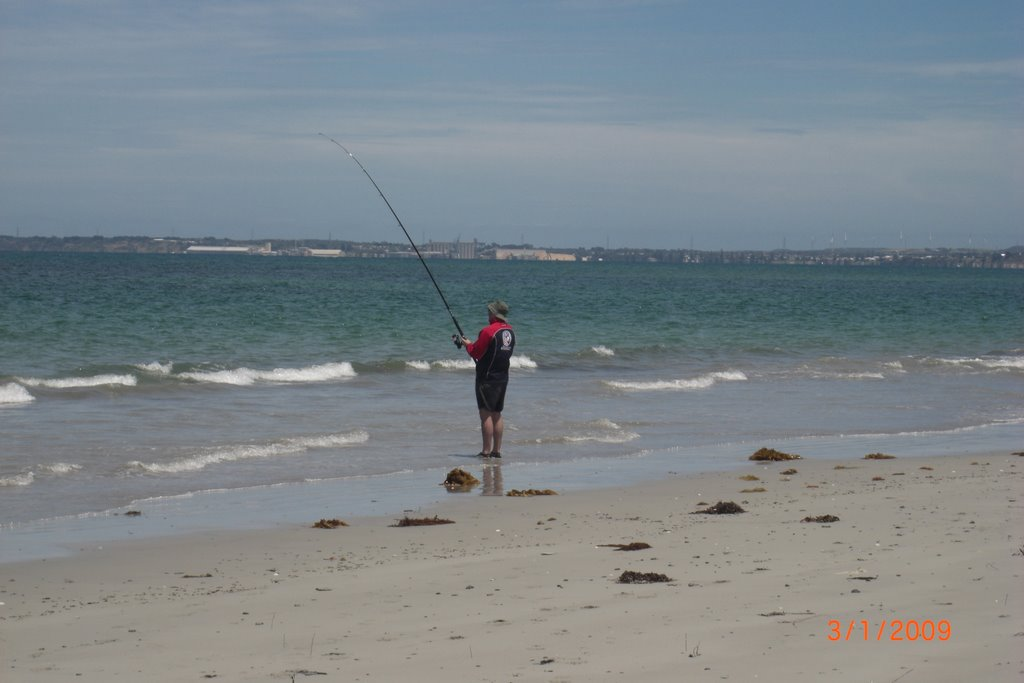 Fisherman at Snapper Point with Portland in distance