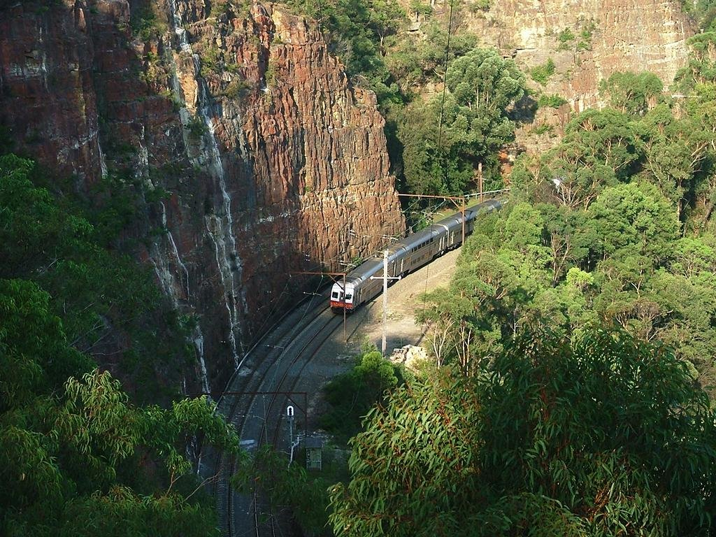 Inter-urban double-deck electric passenger train heading west through the Glenbrook Gorge towards Mount Victoria