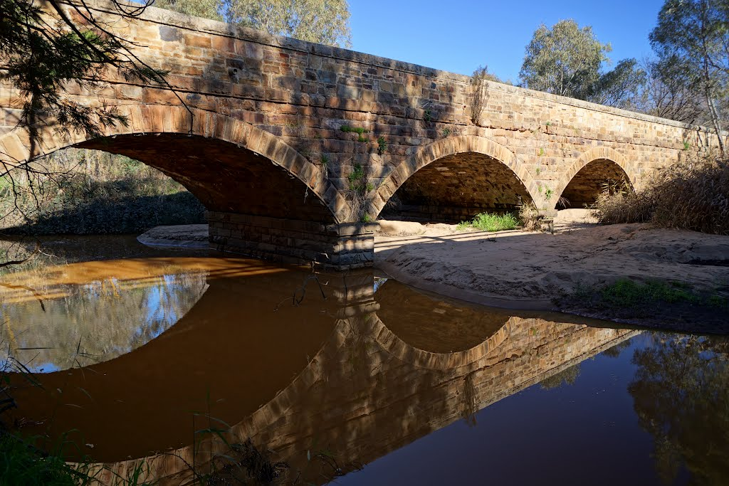 Bridge over Hughes Creek, built in 1850 (2012). Legend has it that a 10-year-old Ned Kelly saved a drowning boy, Richard Shelton, in this creek and was awarded a green sash for doing so. He was wearing this sash when captured at Glenrowan